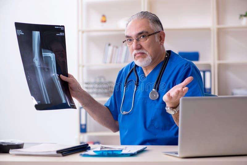 Ο λευκός γενειοφόρος παλαιός ακτινολόγος γιατρών που εργάζεται στην κλινική στοκ εικόνα