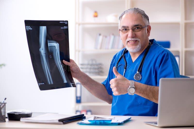 Ο λευκός γενειοφόρος παλαιός ακτινολόγος γιατρών που εργάζεται στην κλινική στοκ εικόνες