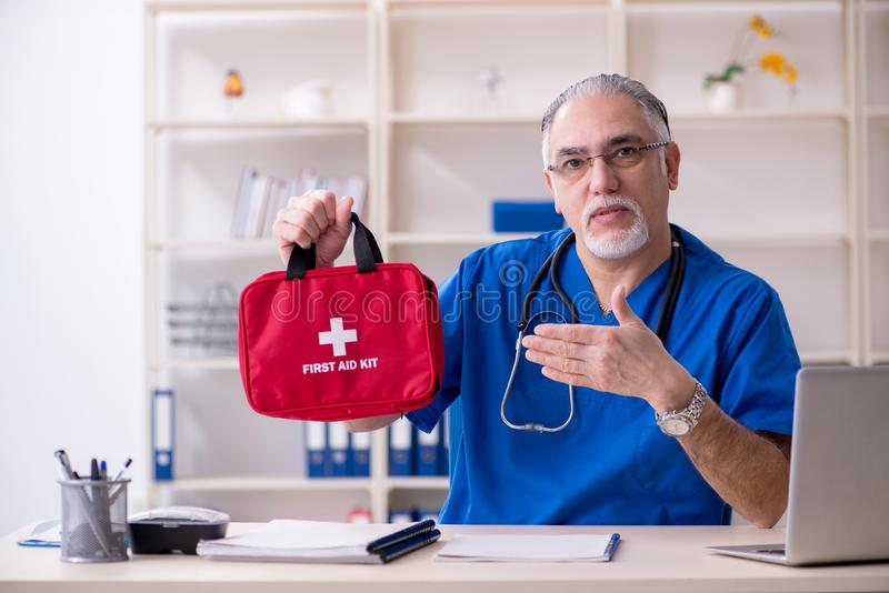 Ο λευκός γενειοφόρος παλαιός γιατρός που εργάζεται στην κλινική στοκ φωτογραφία με δικαίωμα ελεύθερης χρήσης