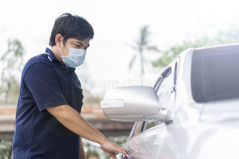 Ο ληστής και ο κλέφτης αυτοκινήτων σε μια μάσκα ανοίγουν την πόρτα του αυτοκινήτου και πειρατεύουν το αυτοκίνητο στοκ φωτογραφία