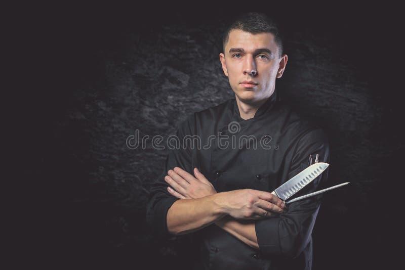 Ο μάγειρας αρχιμαγείρων κρατά ένα μαχαίρι πέρα από το σκοτεινό γκρίζο υπόβαθρο στοκ φωτογραφίες