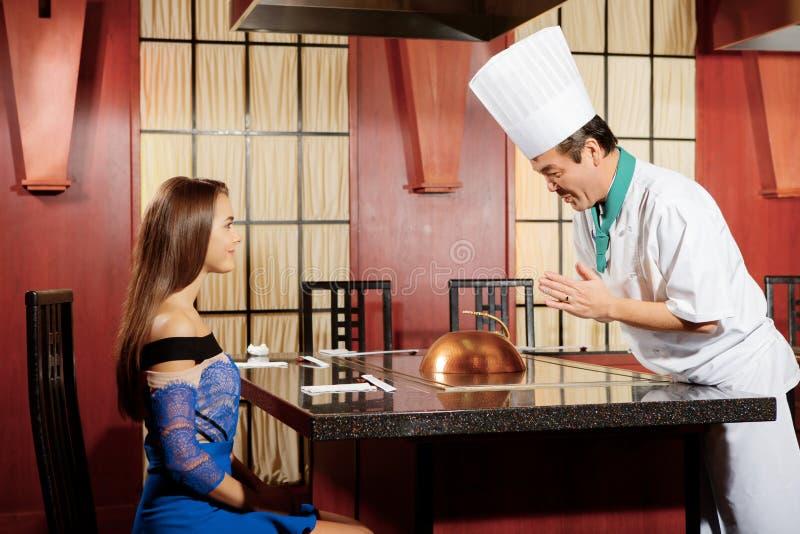 Ο μάγειρας αλληλεπιδρά με έναν θηλυκό φιλοξενούμενο στοκ φωτογραφίες με δικαίωμα ελεύθερης χρήσης