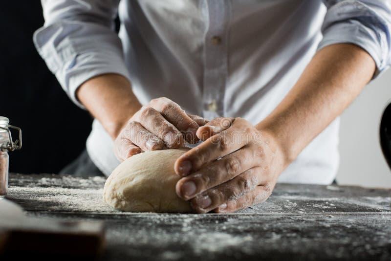 Ο μάγειρας ζυμώνει τη ζύμη με το αλεύρι στον πίνακα κουζινών στοκ φωτογραφίες με δικαίωμα ελεύθερης χρήσης