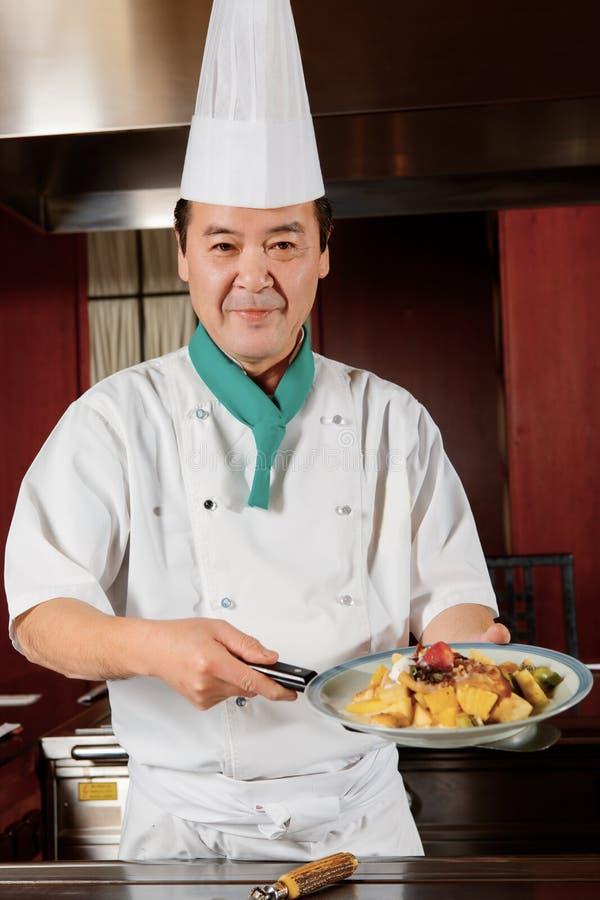Ο μάγειρας καταδεικνύει τα πιάτα του στοκ εικόνες
