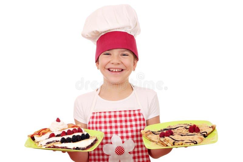 Ο μάγειρας μικρών κοριτσιών με crepes στο πιάτο στοκ εικόνες με δικαίωμα ελεύθερης χρήσης