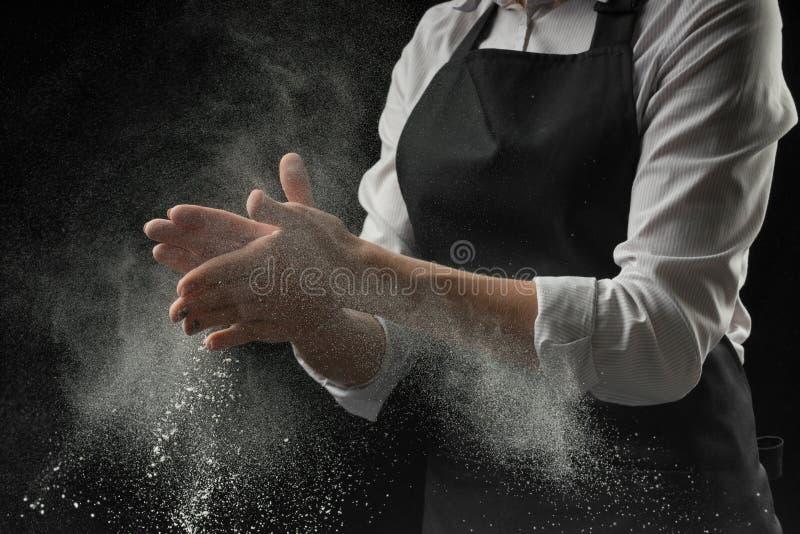 Ο μάγειρας παραδίδει το αλεύρι στο μαύρο έμβλημα υποβάθρου Κατασκευή της πίτσας, των ζυμαρικών, του ψωμιού ψησίματος και των γλυκ στοκ εικόνα με δικαίωμα ελεύθερης χρήσης