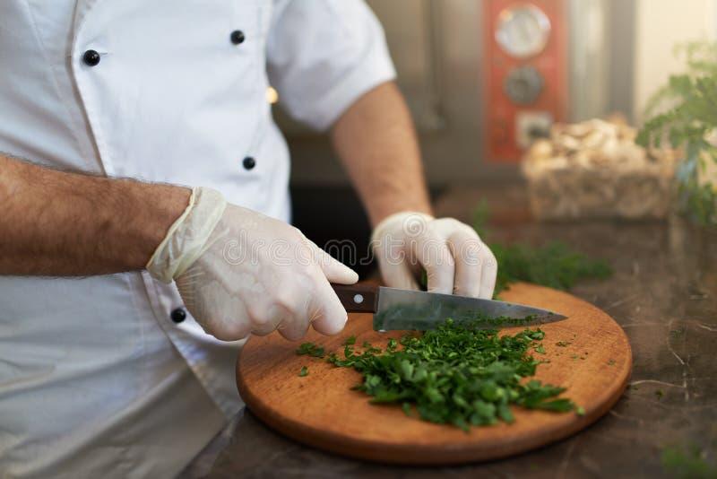 Ο μάγειρας τεμαχίζει τα φρέσκα χορτάρια στον ξύλινο πίνακα στοκ φωτογραφία με δικαίωμα ελεύθερης χρήσης