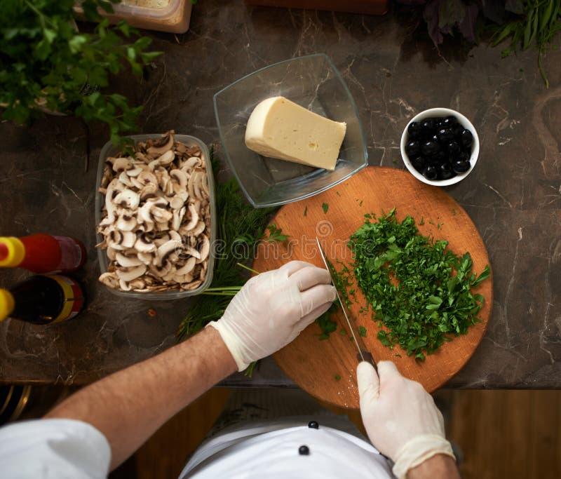 Ο μάγειρας τεμαχίζει την άποψη μαϊντανού firstperson στοκ φωτογραφίες