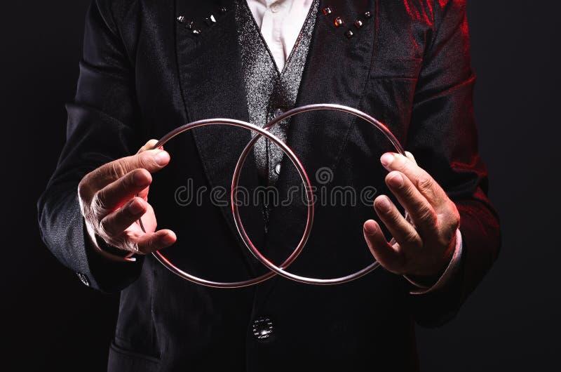 Ο μάγος παρουσιάζει τέχνασμα με τα δαχτυλίδια μετάλλων Χειρισμός με τα στηρίγματα στοκ εικόνες