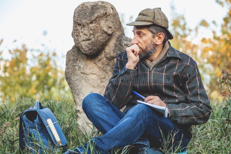 Ο μαθημένος ιστορικός κάθεται πριν από το γλυπτό πετρών στο ανάχωμα στοκ εικόνες με δικαίωμα ελεύθερης χρήσης