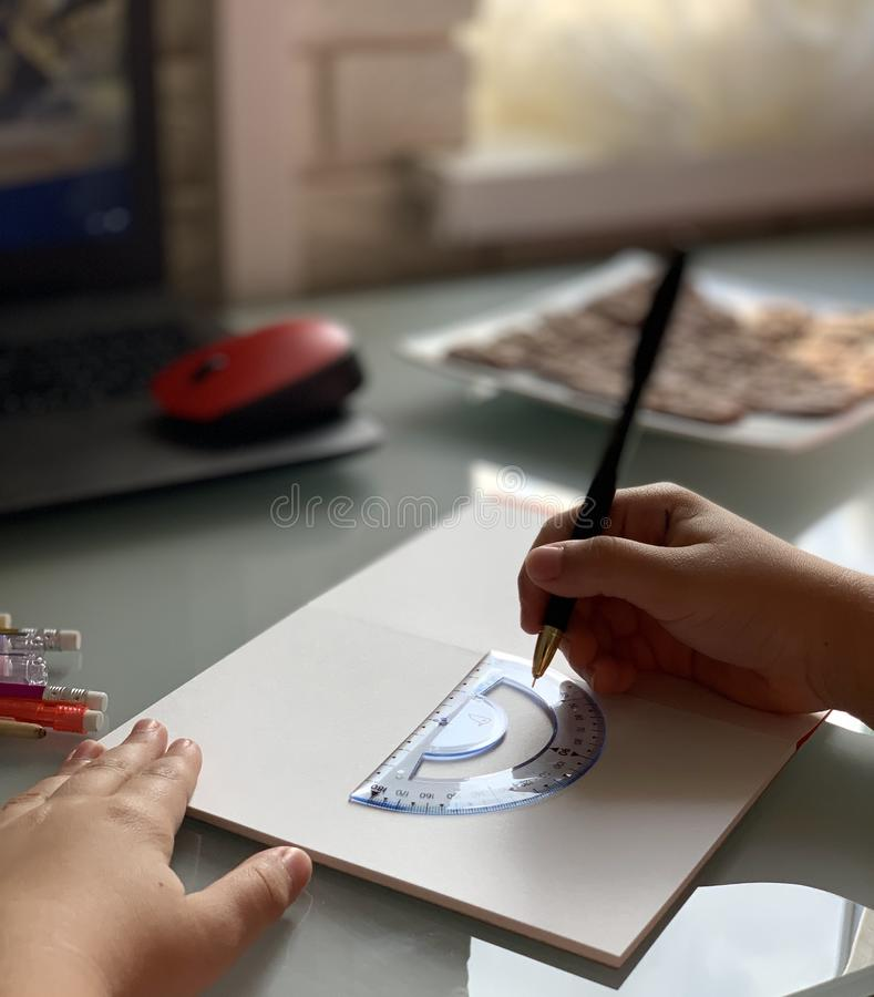 Ο μαθητής κάνει τα μαθήματα Σχολικά θέματα Χέρια παιδιού στοκ εικόνες