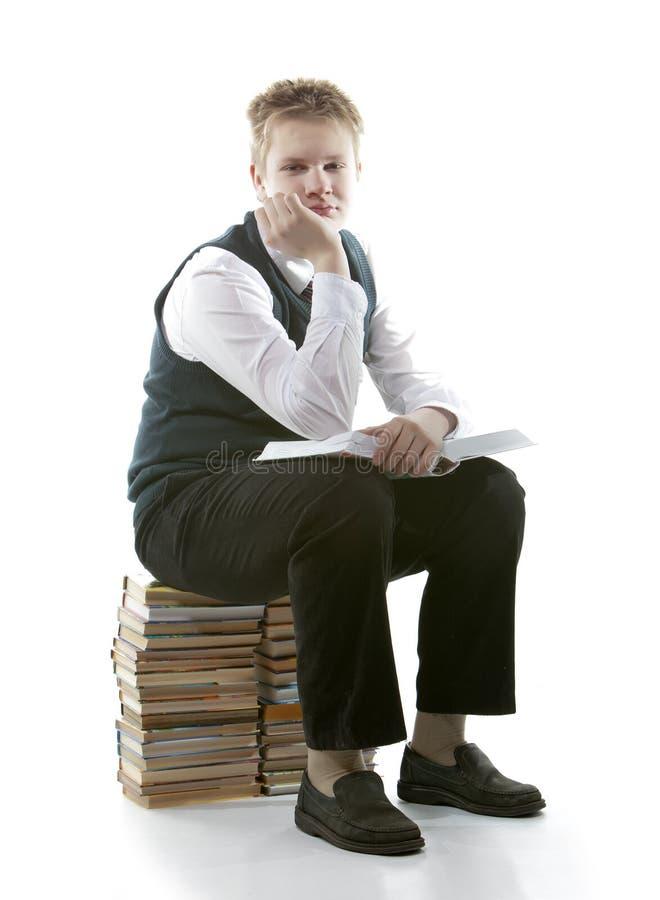 Ο μαθητής σε μια σχολική στολή κάθεται σε ένα πακέτο των βιβλίων, με το ανοιγμένο βιβλίο στα χέρια στοκ εικόνες