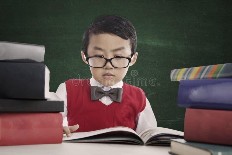 Ο μαθητής Nerd διαβάζει το βιβλίο στοκ εικόνα με δικαίωμα ελεύθερης χρήσης