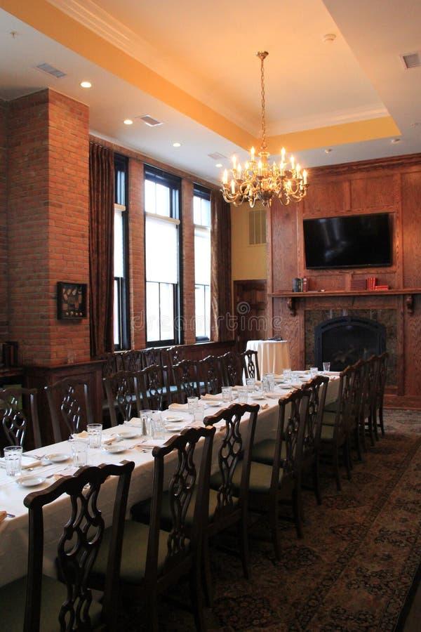 Ο μακριοί σκοτεινοί ξύλινοι πίνακας και οι καρέκλες στη τραπεζαρία θέτουν για το κόμμα, το εστιατόριο Harvey και το φραγμό, Sarat στοκ εικόνες