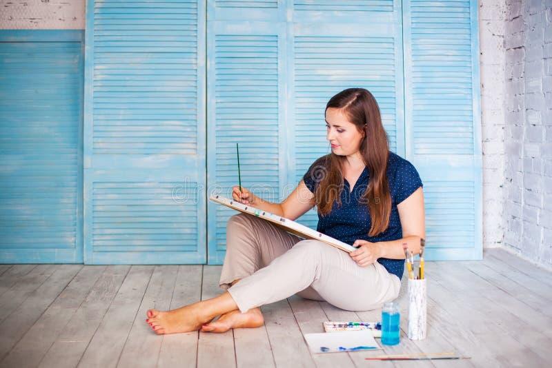 Ο μακρυμάλλης θηλυκός καλλιτέχνης χρωματίζει κάτι στον καμβά στοκ φωτογραφία με δικαίωμα ελεύθερης χρήσης