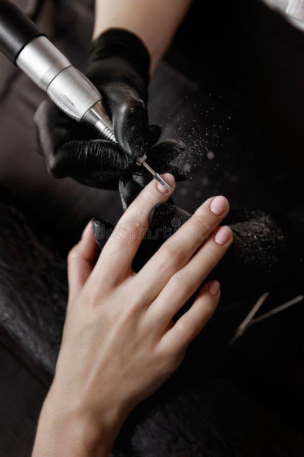 Ο μανικιουρίστας στα μαύρα γάντια, αλέθοντας μηχανή αφαιρεί το παλαιό πήκτωμα στίλβωση στοκ φωτογραφία