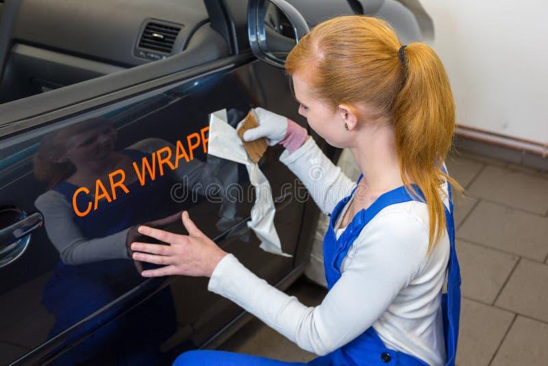 Ο μαρκάροντας ειδικός αυτοκινήτων βάζει το λογότυπο με την τυλίγοντας ταινία αυτοκινήτων στο αυτοκίνητο στοκ φωτογραφίες με δικαίωμα ελεύθερης χρήσης