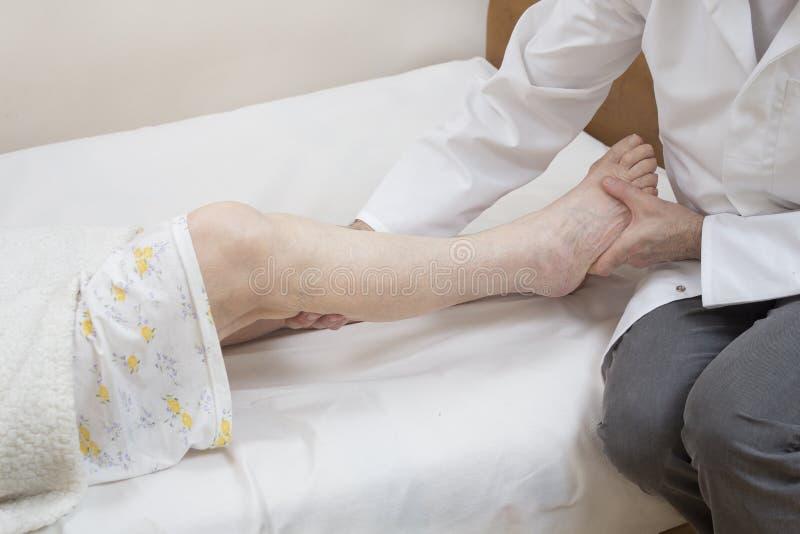 Ο μασέρ τρίβει το μόσχο μιας ηλικιωμένης γυναίκας σε ένα κρεβάτι σε ένα άσπρο φύλλο στοκ φωτογραφίες