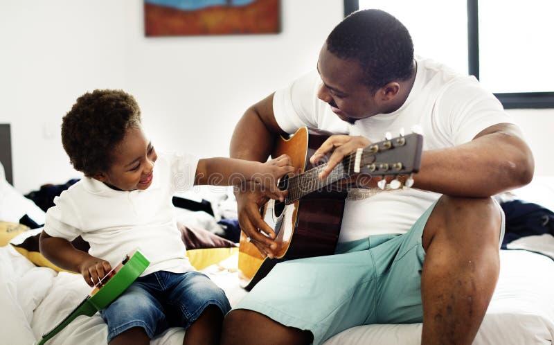 Ο μαύρος πατέρας απολαμβάνει την κιθάρα με το παιδί του happin μαζί στοκ φωτογραφία