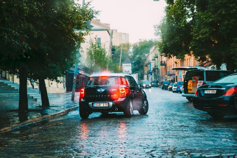 Ο μαύρος χωρικός του Mini Cooper αυτοκινήτων χρώματος πηγαίνει στη βροχή στην οδό στοκ εικόνα