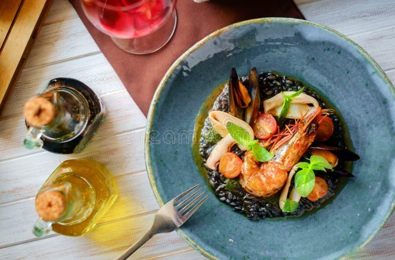 Ο Μαύρος risotto θαλασσινών στο πιάτο σε ένα ξύλινο υπόβαθρο, τοπ άποψη στοκ εικόνα με δικαίωμα ελεύθερης χρήσης