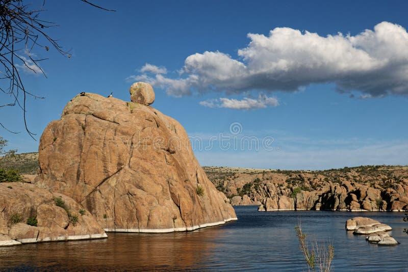 Ο μεγάλος λίθος με το μικρό βράχο στην κορυφή, κάθεται στη μέση μιας μπλε λίμνης στοκ εικόνες