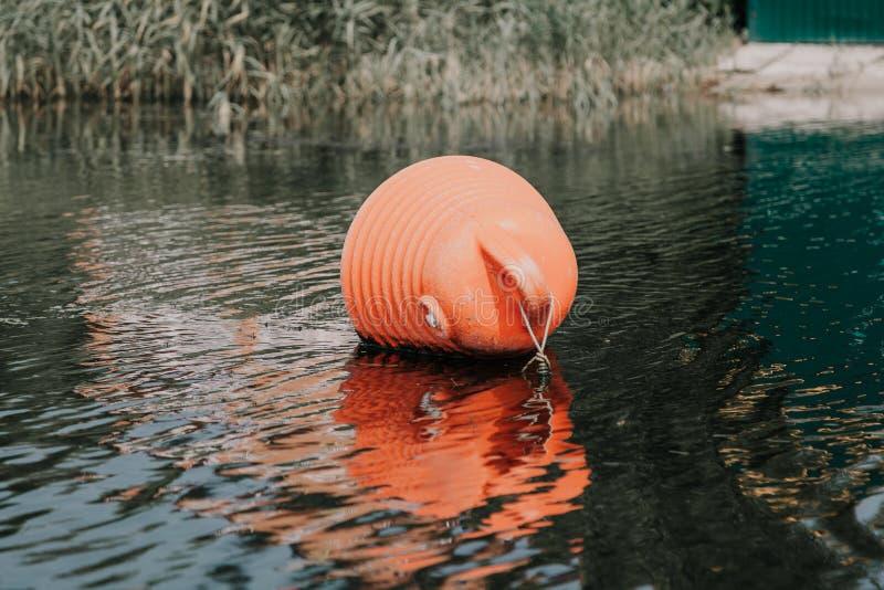 Ο μεγάλος πορτοκαλής σημαντήρας βρίσκεται στο νερό στοκ εικόνα