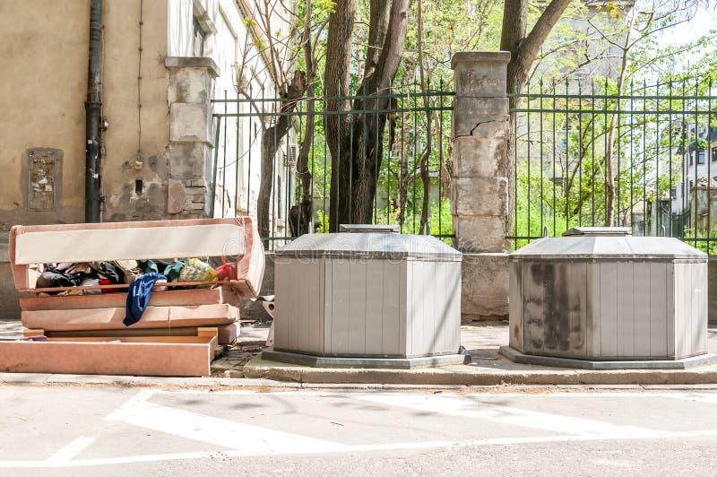 Ο μεγάλος σωρός των απορριμάτων και των παλιοπραγμάτων πέταξε στην οδό κοντά σε δύο υπόγεια δοχεία dumpster στοκ φωτογραφίες