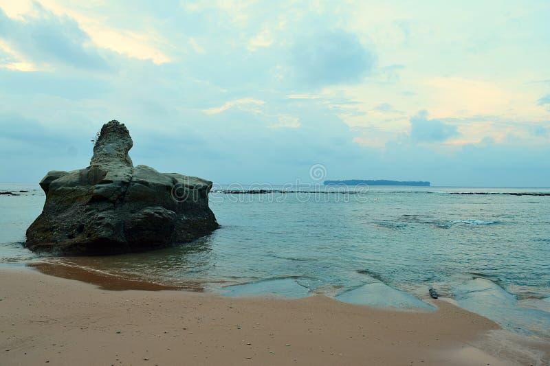 Ο μεγάλος Stone στα ήρεμα νερά θάλασσας στην παλιή αμμώδη παραλία με τα χρώματα στο νεφελώδη ουρανό πρωινού - Sitapur, νησί του N στοκ εικόνα με δικαίωμα ελεύθερης χρήσης