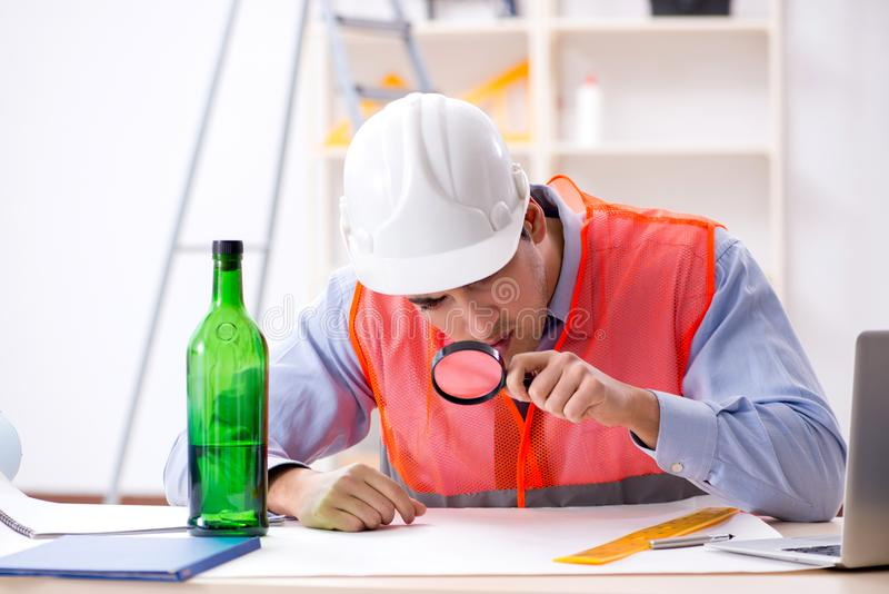 Ο μεθυσμένος μηχανικός που εργάζεται στο εργαστήριο στοκ εικόνες