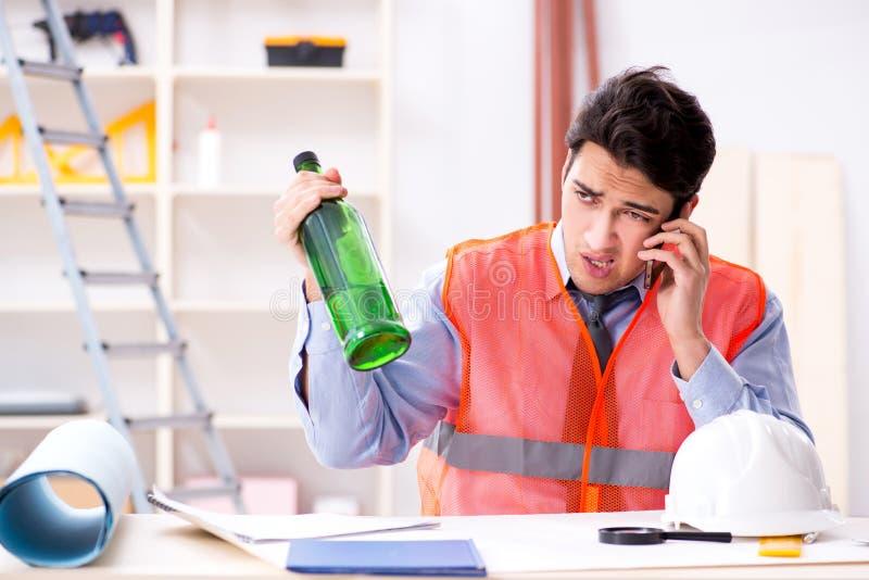 Ο μεθυσμένος μηχανικός που εργάζεται στο εργαστήριο στοκ εικόνα