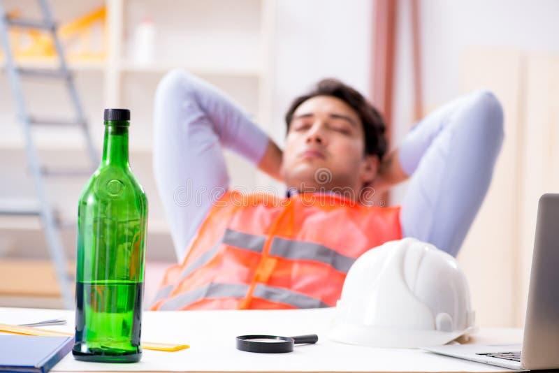 Ο μεθυσμένος μηχανικός που εργάζεται στο εργαστήριο στοκ φωτογραφία