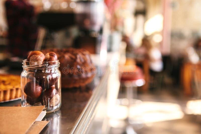 Ο μετρητής στον καφέ είναι ένα θολωμένο υπόβαθρο Καρύδια στην τράπεζα στο πρώτο πλάνο, εσωτερικό του καφέ στοκ εικόνες με δικαίωμα ελεύθερης χρήσης