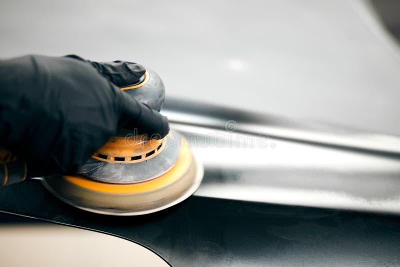Ο μηχανικός αλέθει το μέρος αυτοκινήτων για τη ζωγραφική Αυτόματο χρώμα επισκευής εργασίας σωμάτων αυτοκινήτων μετά από το ατύχημ στοκ φωτογραφία με δικαίωμα ελεύθερης χρήσης