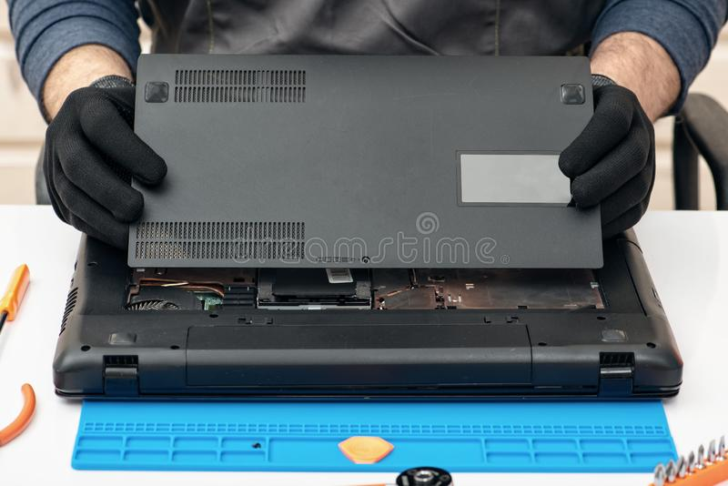 Ο μηχανικός αποσυναρμολογεί τις λεπτομέρειες ενός σπασμένου lap-top για την επισκευή στοκ φωτογραφία