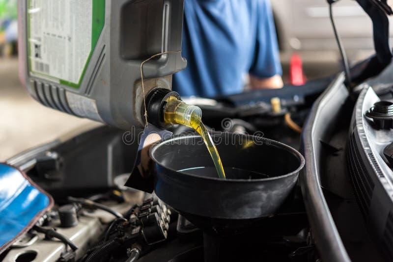 Ο μηχανικός αυτοκινήτων γεμίζει ένα φρέσκο πετρέλαιο μηχανών λιπαντικών στοκ φωτογραφία με δικαίωμα ελεύθερης χρήσης