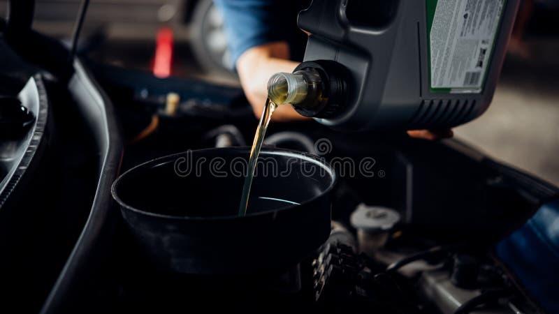 Ο μηχανικός αυτοκινήτων γεμίζει ένα φρέσκο πετρέλαιο μηχανών λιπαντικών στοκ εικόνες