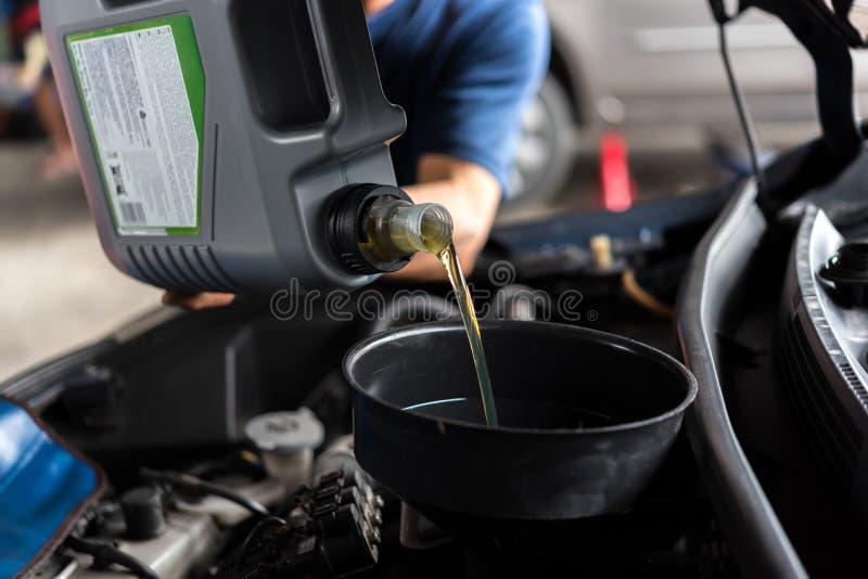 Ο μηχανικός αυτοκινήτων γεμίζει ένα φρέσκο πετρέλαιο μηχανών λιπαντικών στοκ εικόνα