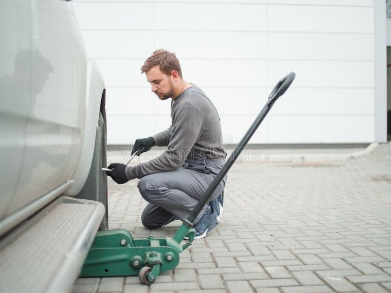 Ο μηχανικός αφαιρεί τη ρόδα από το αυτοκίνητο υπαίθρια στοκ εικόνα με δικαίωμα ελεύθερης χρήσης
