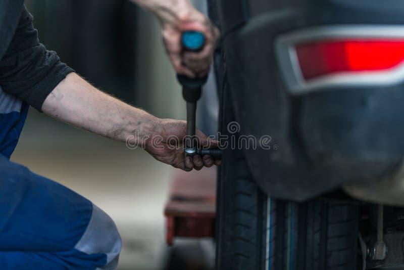 Ο μηχανικός αλλάζει τις ρόδες σε ένα σύγχρονο αυτοκίνητο στοκ φωτογραφία