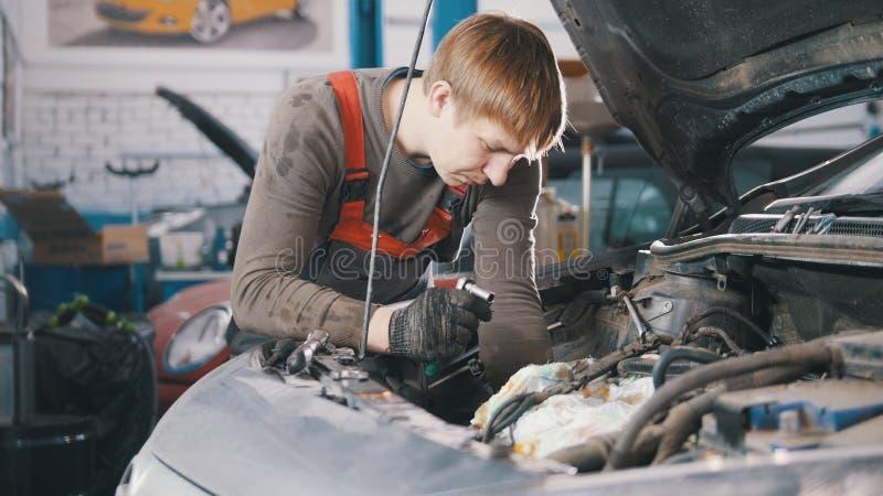 Ο μηχανικός ελέγχει και επισκευάζει την αυτοκίνητη μηχανή, επισκευή αυτοκινήτων, που λειτουργεί στο εργαστήριο, εξέταση, κάτω από στοκ εικόνα