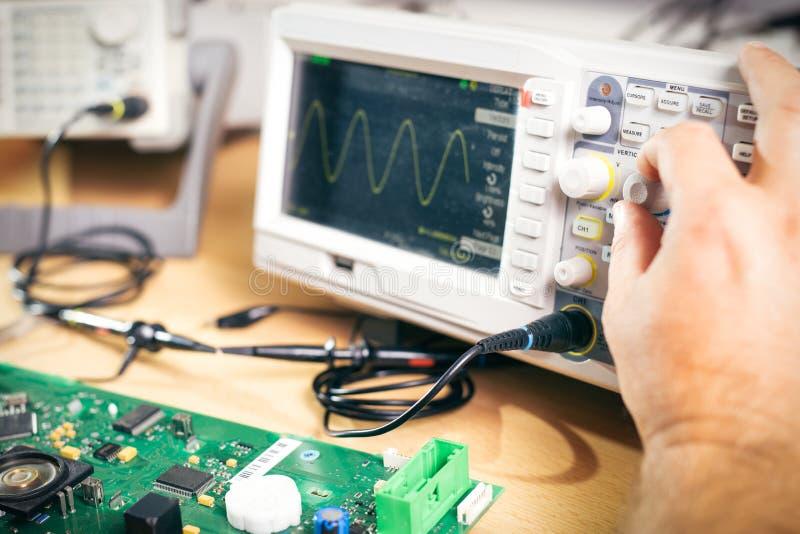 Ο μηχανικός εξετάζει τα ηλεκτρονικά συστατικά με τον παλμογράφο στο κέντρο υπηρεσιών στοκ εικόνες