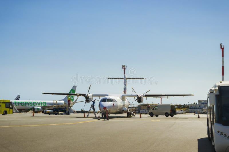 Ο μηχανικός εξυπηρετεί δύο αεροσκάφη μηχανή-προωστήρων σε Ηράκλειο Airpo στοκ εικόνες