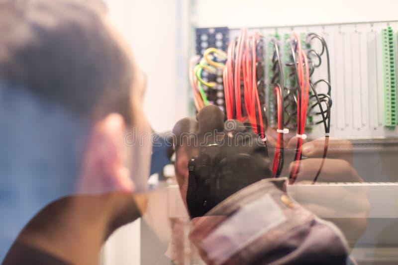 Ο μηχανικός ηλεκτρολόγων εξετάζει τις ηλεκτρικές εγκαταστάσεις στον ηλεκτρονόμο υπέρ στοκ εικόνες