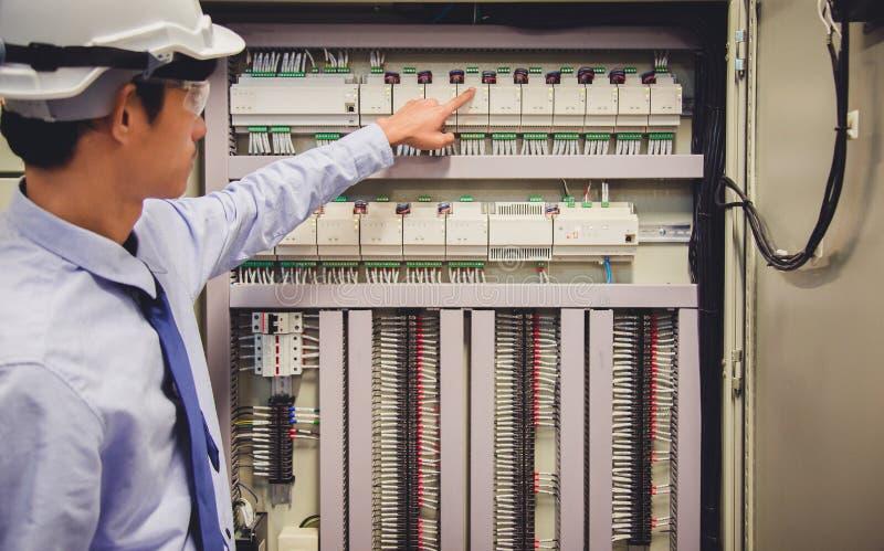 Ο μηχανικός ηλεκτρολόγων εξετάζει τον ηλεκτρικό πίνακα ελέγχου εγκαταστάσεων παραγωγής ενέργειας εγκαταστάσεων στοκ φωτογραφίες