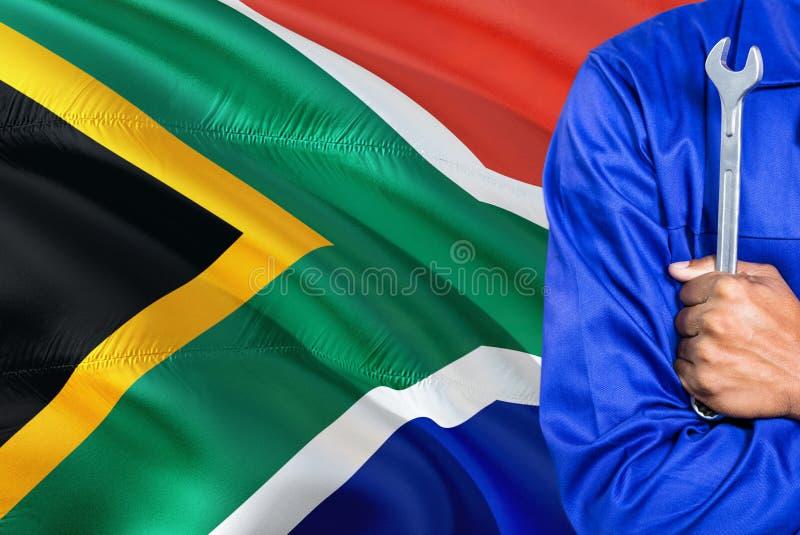 Ο μηχανικός μπλε σε ομοιόμορφο κρατά το γαλλικό κλειδί στο κυματίζοντας κλίμα σημαιών της Νότιας Αφρικής Διασχισμένος τεχνικός όπ στοκ εικόνες