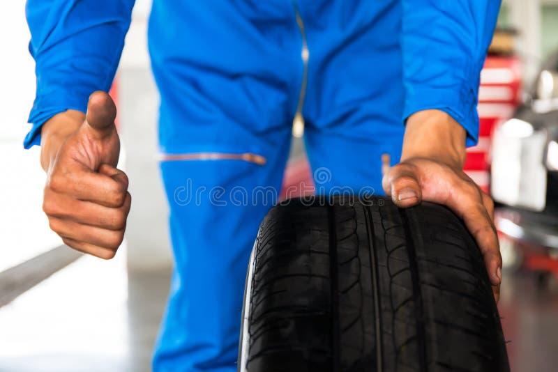 Ο μηχανικός που κρατά μια ρόδα αυτοκινήτων με τον αντίχειρα υπογράφει επάνω στο SE γκαράζ αυτοκινήτων στοκ εικόνες με δικαίωμα ελεύθερης χρήσης