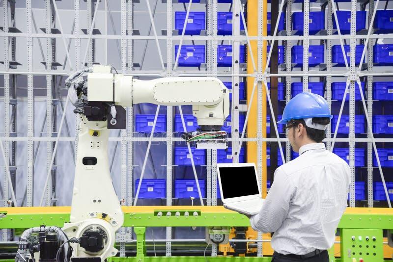 Ο μηχανικός προγραμματιστών ελέγχει το ρομπότ για τη λογιστική αποθήκη εμπορευμάτων στοκ εικόνα με δικαίωμα ελεύθερης χρήσης