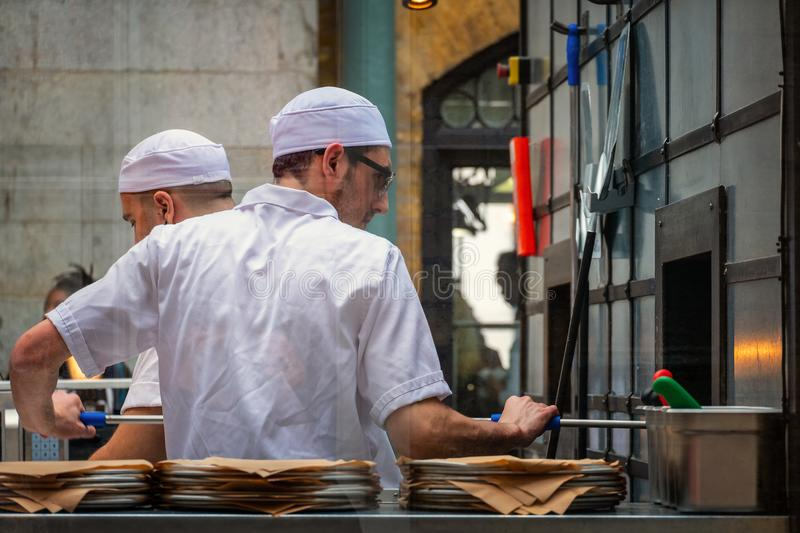 Ο μη αναγνωρισμένος αρχιμάγειρας ψήνει το πιάτο των πιτσών σε ένα ιταλικό εστιατόριο στην αγορά κήπων Covent στοκ φωτογραφία με δικαίωμα ελεύθερης χρήσης