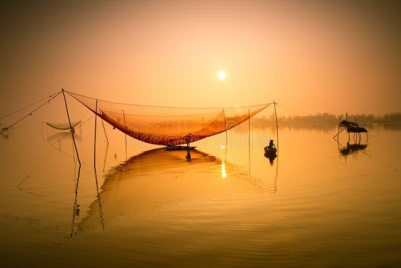 Ο μη αναγνωρισμένος ψαράς ελέγχει τα δίχτυα του στα ξημερώματα στον ποταμό σε Hoian, Βιετνάμ